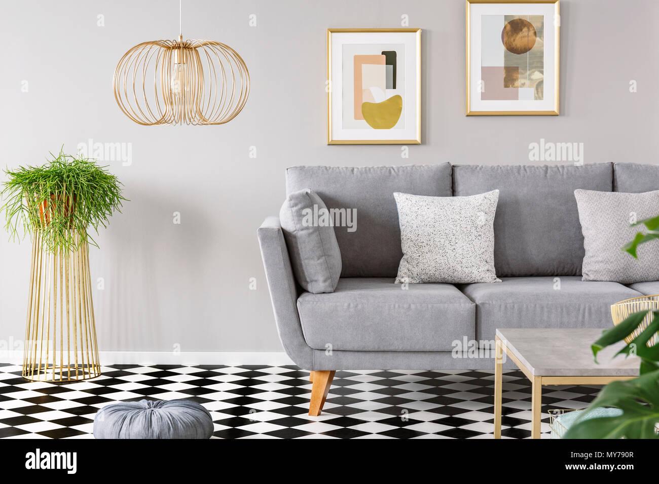 Real Photo Aus Einem Wohnzimmer Interieur Mit Gold Poster An Den Wänden,  Grau Sofa Mit Kissen Und Karierten Boden