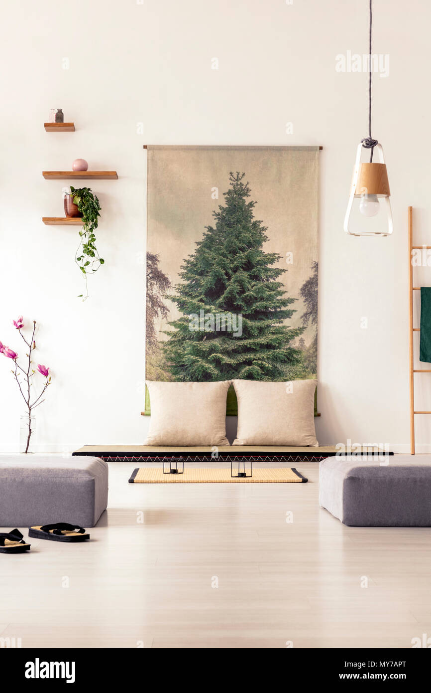 Elegantes Wohnzimmer Einrichtung Mit Einem Großen Plakat An Der Wand, Grau  Hocker, Futon, Kissen Und Lampe