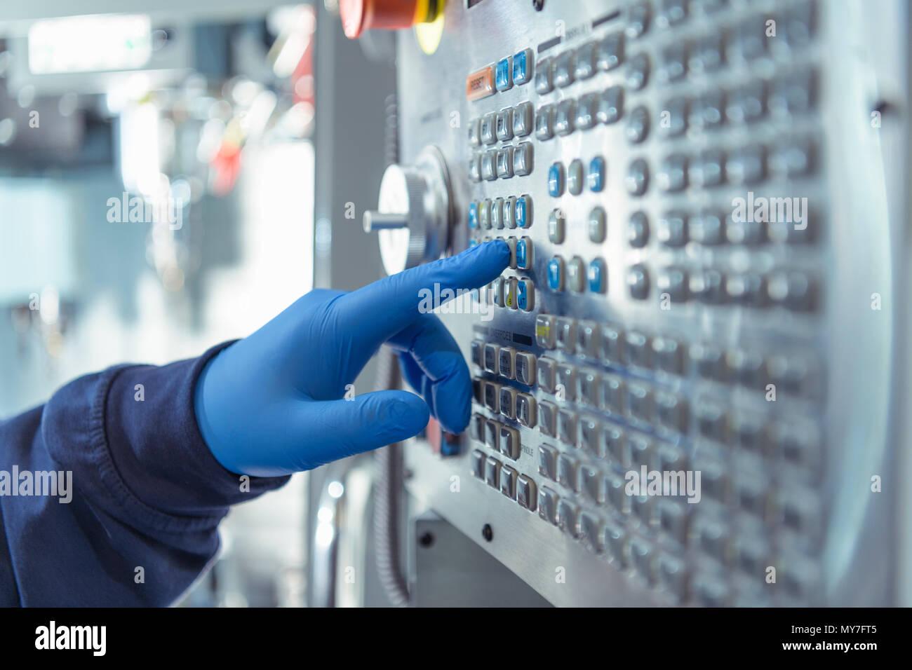Nahaufnahme von Ingenieur durch Drücken der Taste auf dem Bedienfeld in der Maschinenfabrik Stockbild