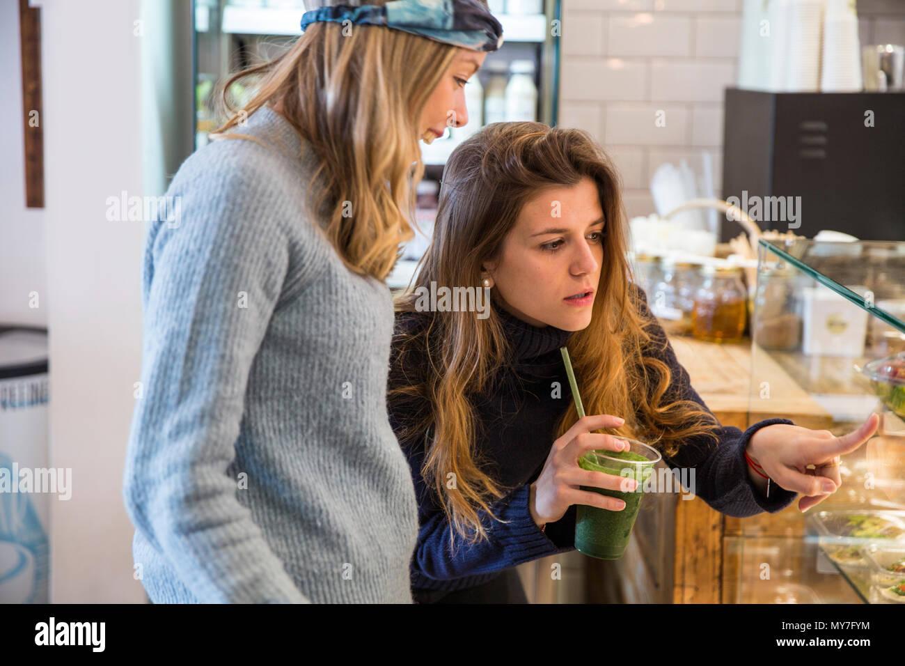 Junge Frau und Freund auf frische Lebensmittel Vitrine im Cafe Stockbild