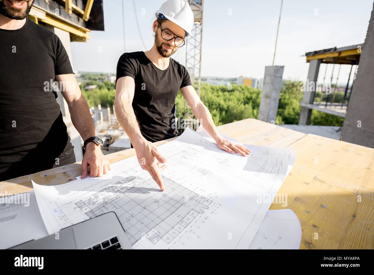 Arbeitnehmer mit Zeichnungen auf der Baustelle Stockbild