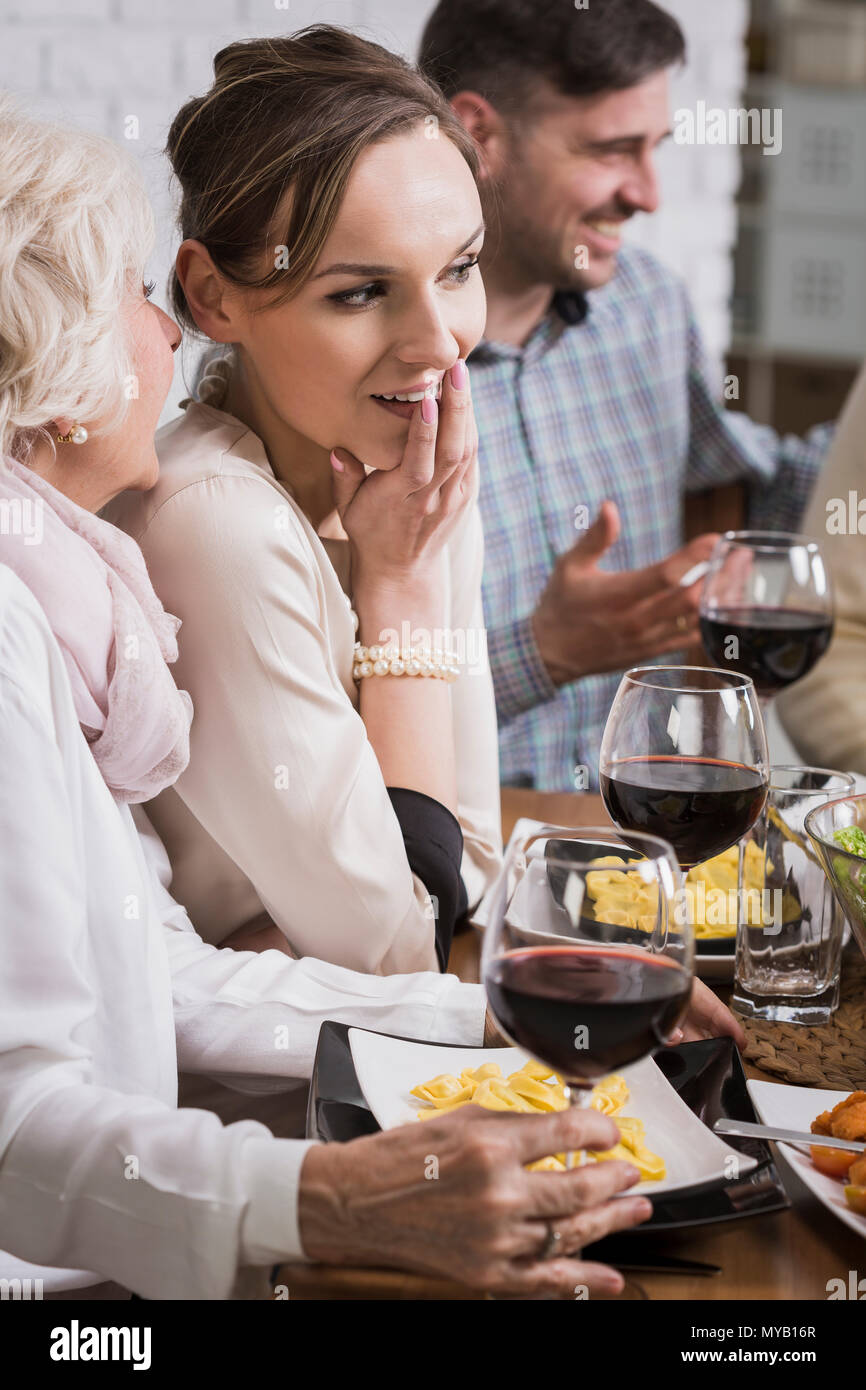 Reife Frau flüstert zu junge Frau, sitzen neben Tisch beim Abendessen mit der Familie Stockfoto