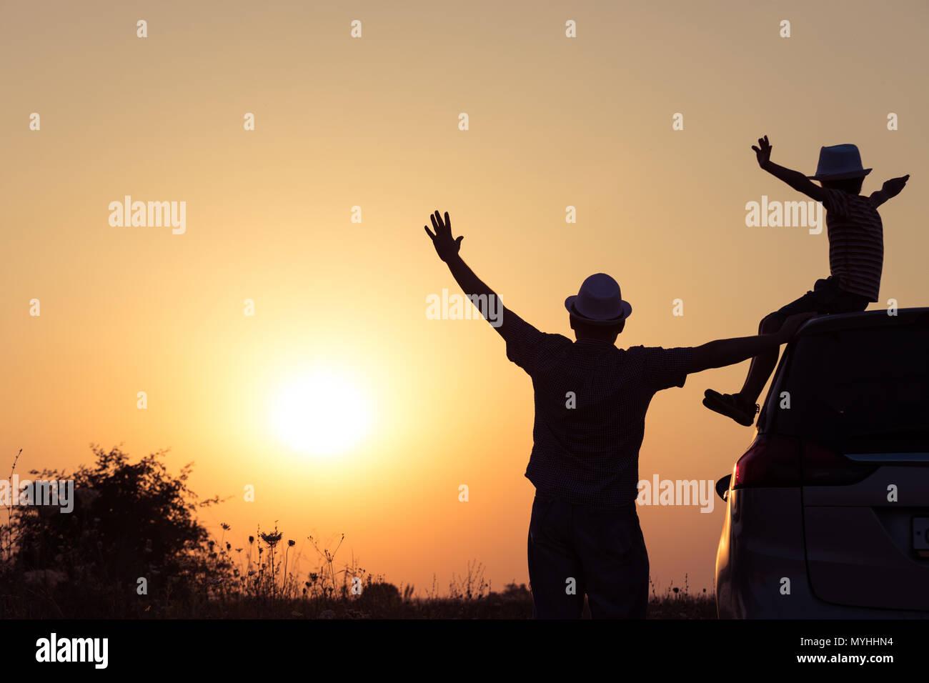 Vater und Sohn spielen im Park bei Sonnenuntergang. Leute, die Spaß auf dem Feld. Konzept der freundliche Familie und der Sommerferien. Stockbild