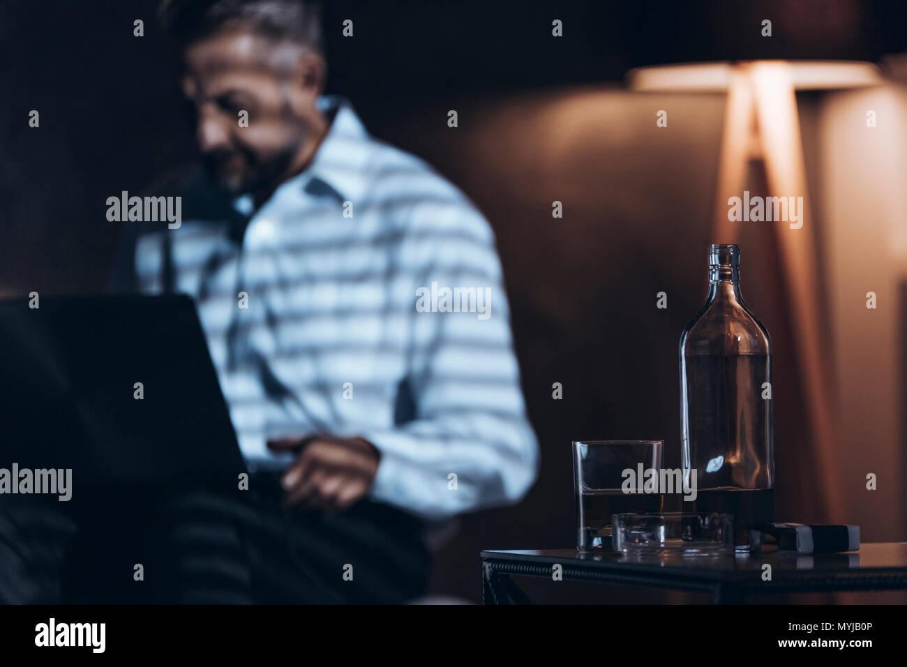 In der Nähe von Glas Flasche mit Alkohol. Workaholic mit Alkohol Problem Stockfoto