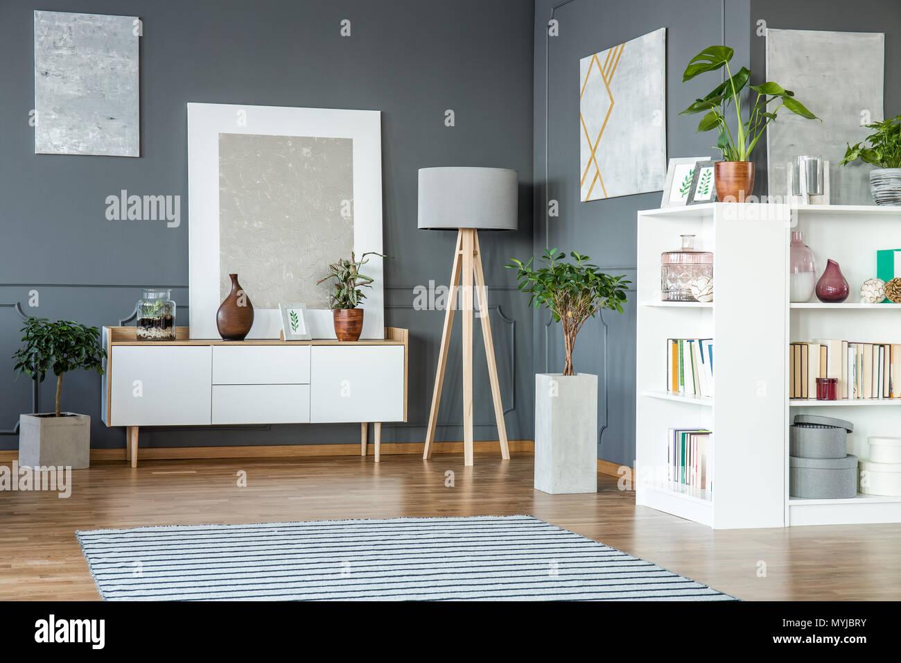 Weißen Schrank und Regale, Holz- Lampe und Gemälde auf die graue ...