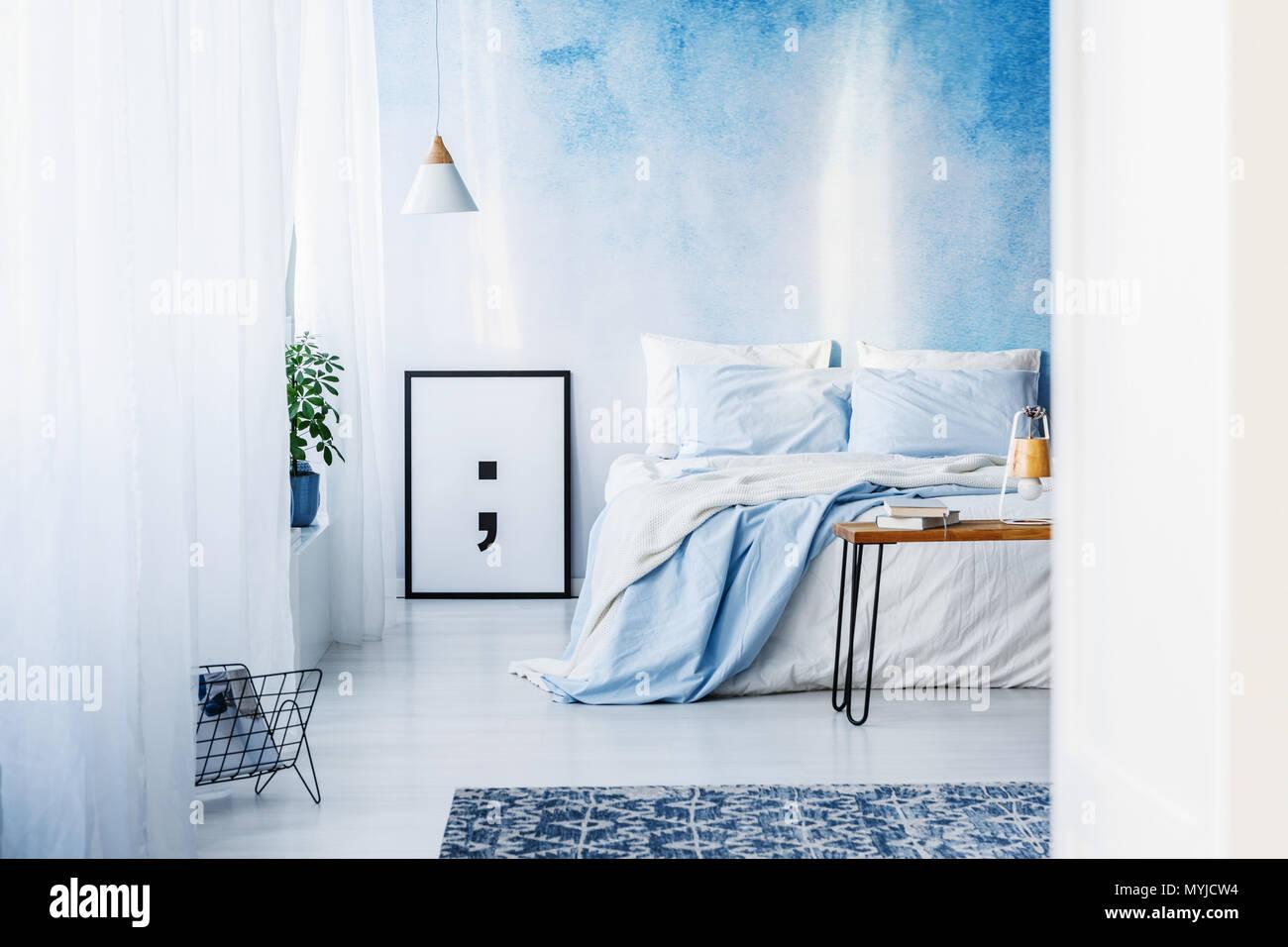 Teppich und Poster im blauen Schlafzimmer mit Bett gegen ...