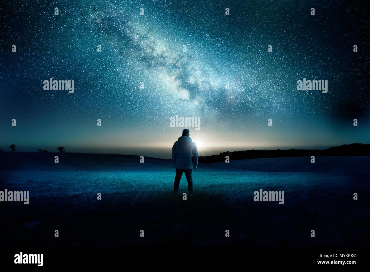 Ein Mann steht gerade mit Verwunderung und Erstaunen, wie der Mond und die Milchstraße die Nacht Himmel füllen. Nacht Landschaft. Foto Composite. Stockbild
