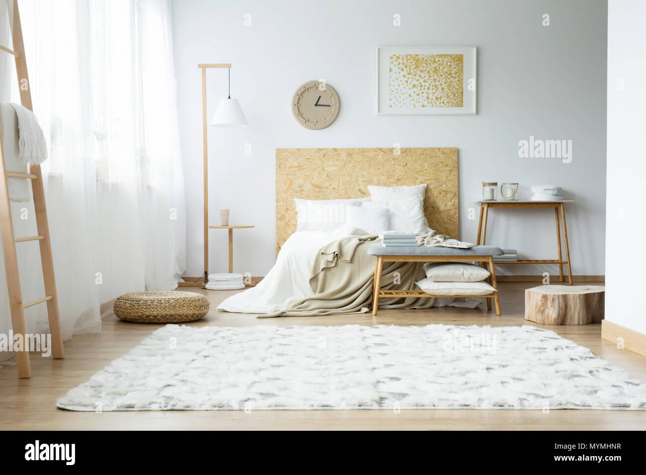 Hellen Teppich Pouf Und Holz Stumpf In Ein Geraumiges Schlafzimmer