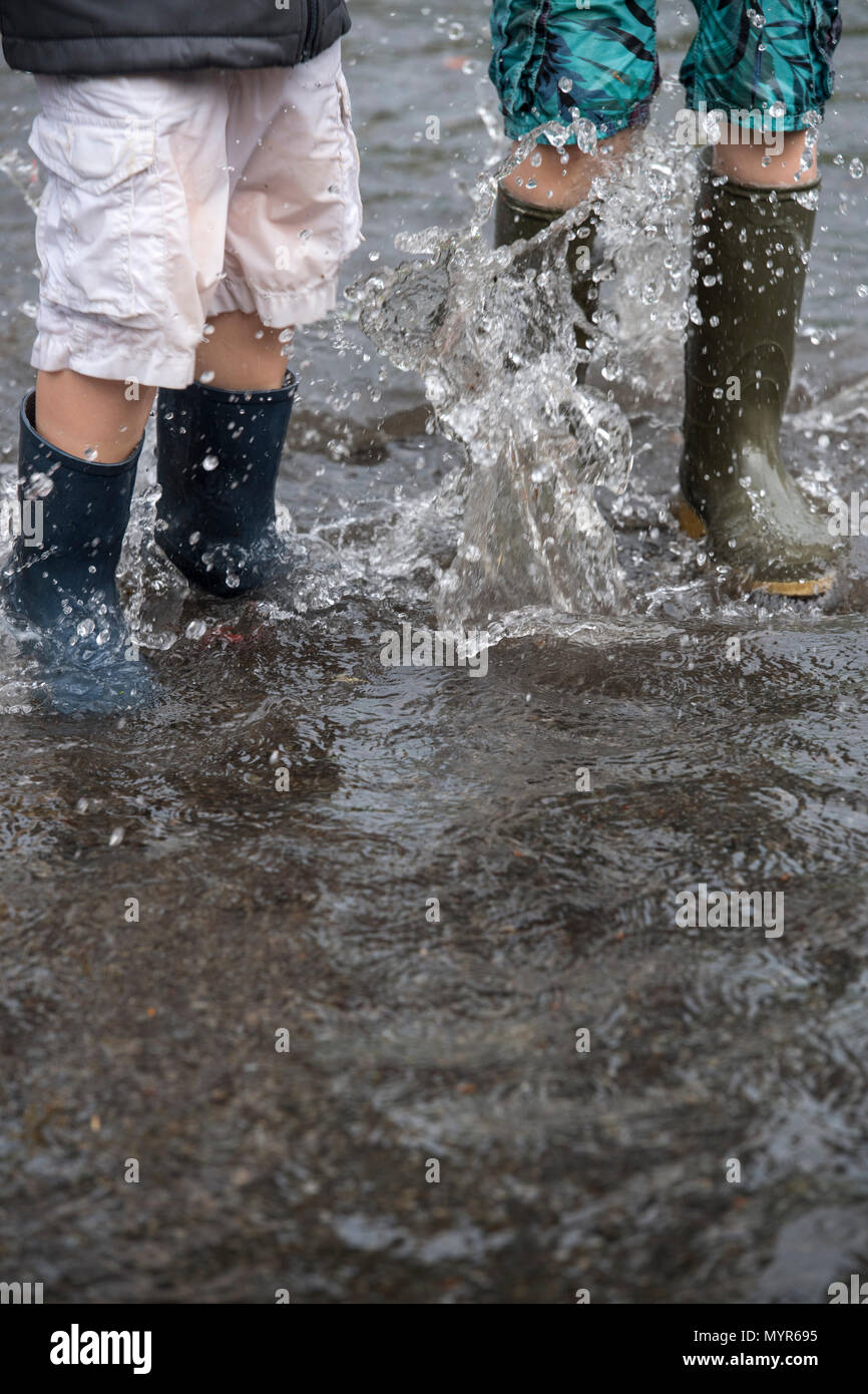 Jungen tragen Gummistiefel Spritzen in das Hochwasser in einer Straße nach schweren Regenfällen Stockbild
