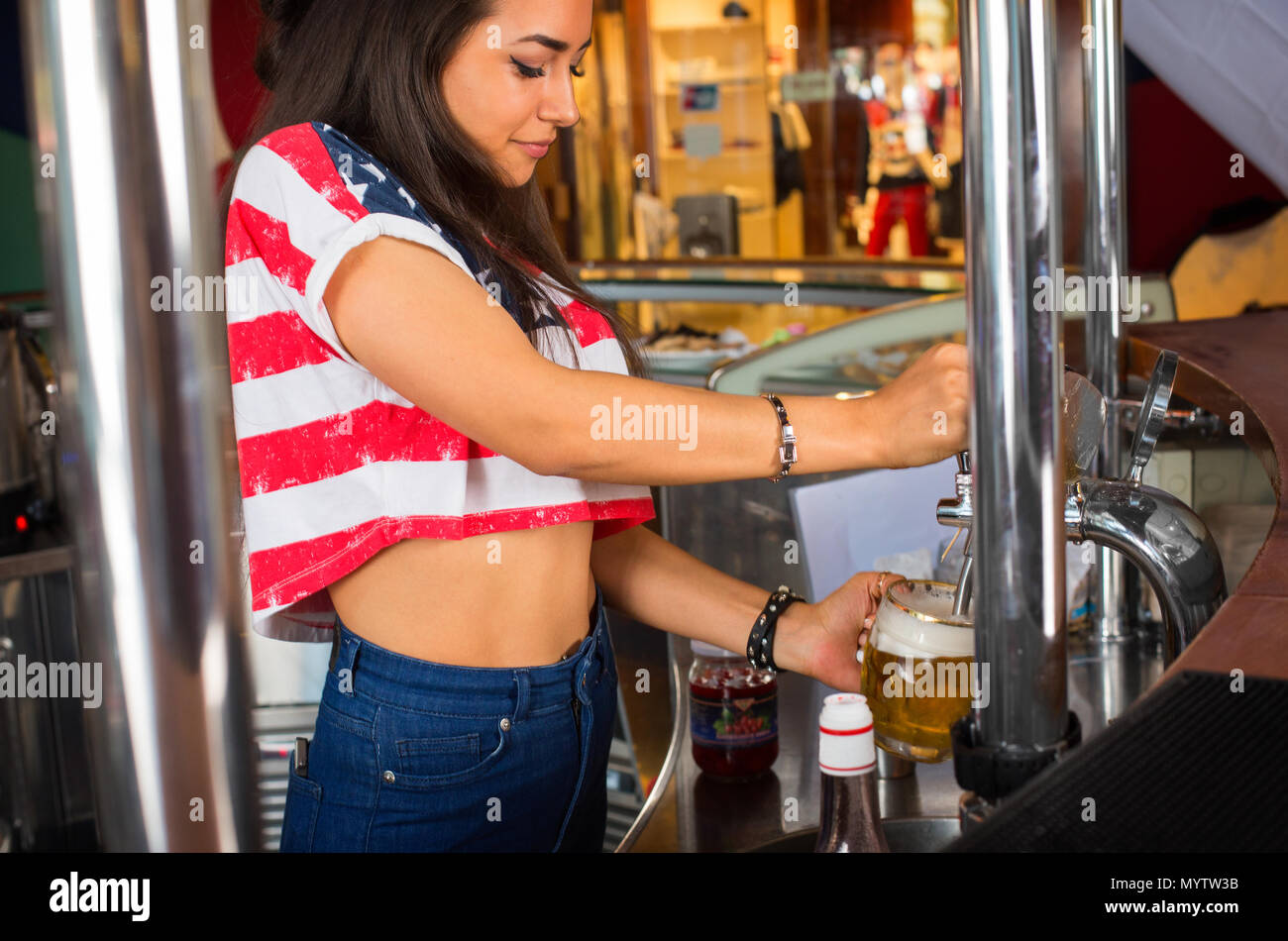 Hübschen weiblichen Barkeeper Bier zapfen von an der Bar tippen Stockbild