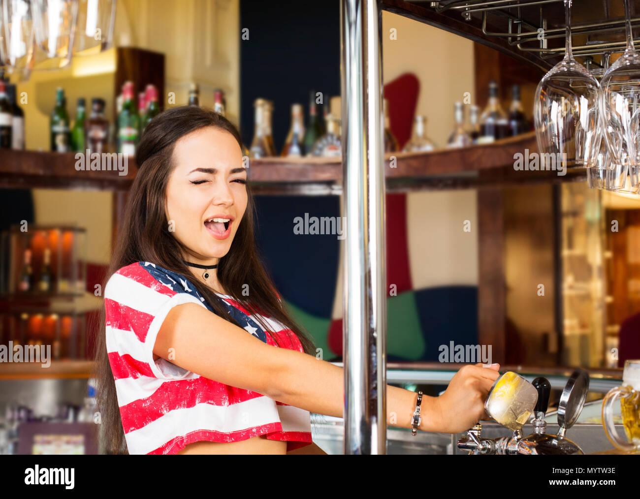 Freudige weiblichen Barkeeper Bier zapfen von an der Bar tippen Stockbild