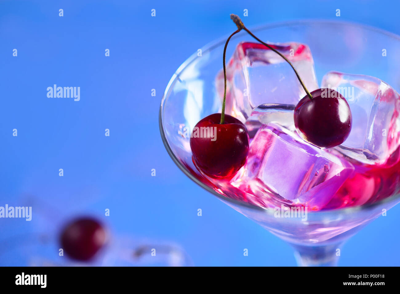 Cherry cocktail Close-up. Martini Glas mit Eiswürfeln und Kirschen auf einem blauen Hintergrund mit kopieren. Heißer Sommertag Erfrischung Konzept Stockbild