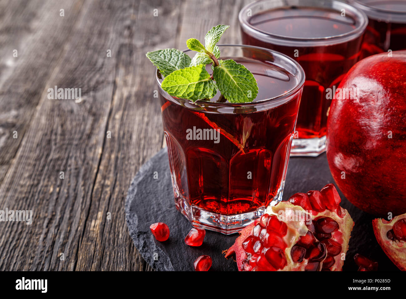 Glas Granatapfelsaft mit frischer Granatapfel Obst und Minze auf Holztisch, gesundes Getränk Konzept. Stockbild
