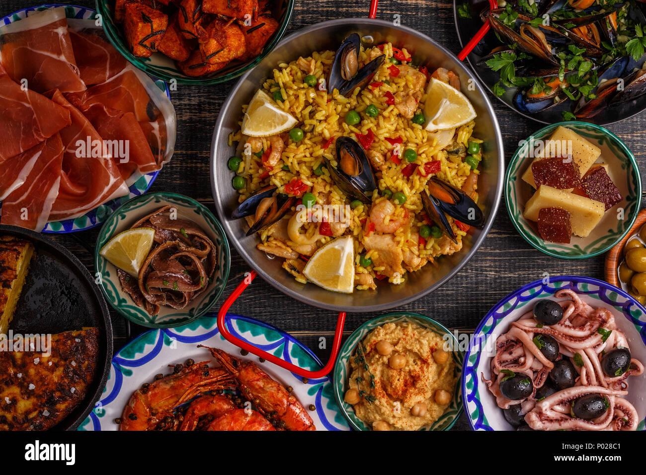 Typische spanische Tapas Konzept. Konzept gehören Scheiben jamon, Schüsseln mit Oliven, Sardellen, würzige Kartoffeln, pürierte Kichererbsen, Garnelen, Tintenfisch, der manche Stockbild