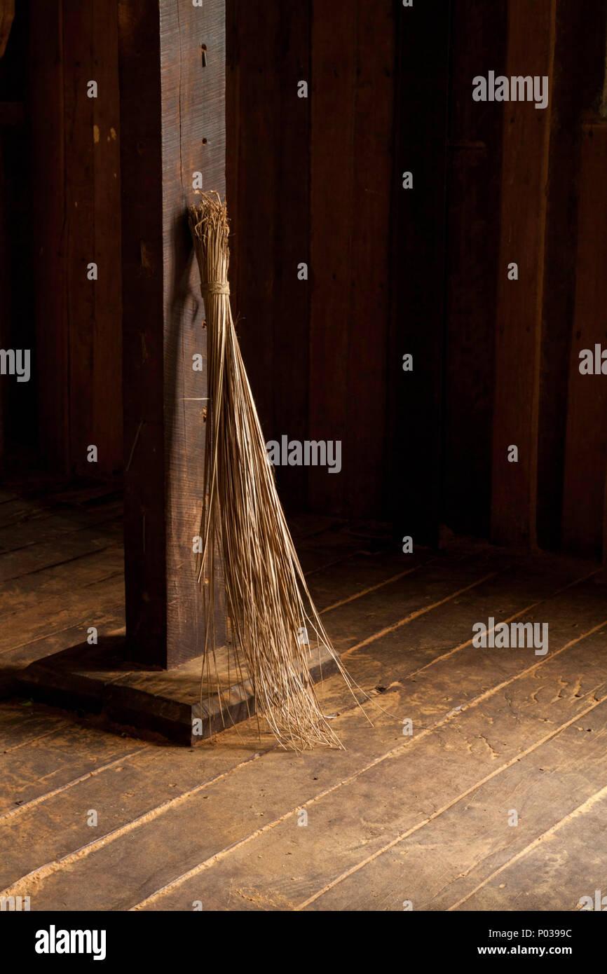 Alte Bürste oder Besen proppped gegen einen Holzbalken in der ...