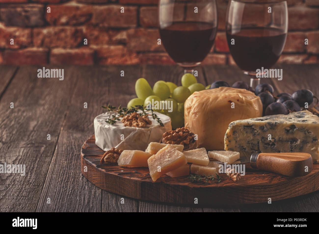 Käse, Nüsse, Trauben und Rotwein auf Holz- Hintergrund, selektive konzentrieren. Stockbild