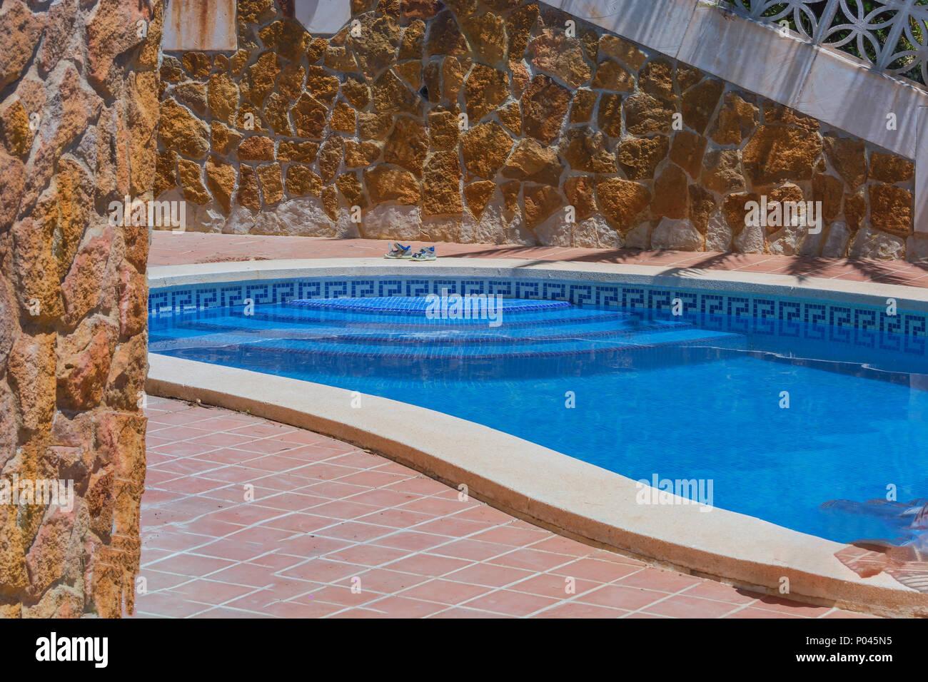 Luxus Schwimmbad Mit Der Wunderschönen Landschaft Des Gebietes. Im  Hintergrund Eine Mediterrane Wand Dekoriert Mit Sandsteinen.