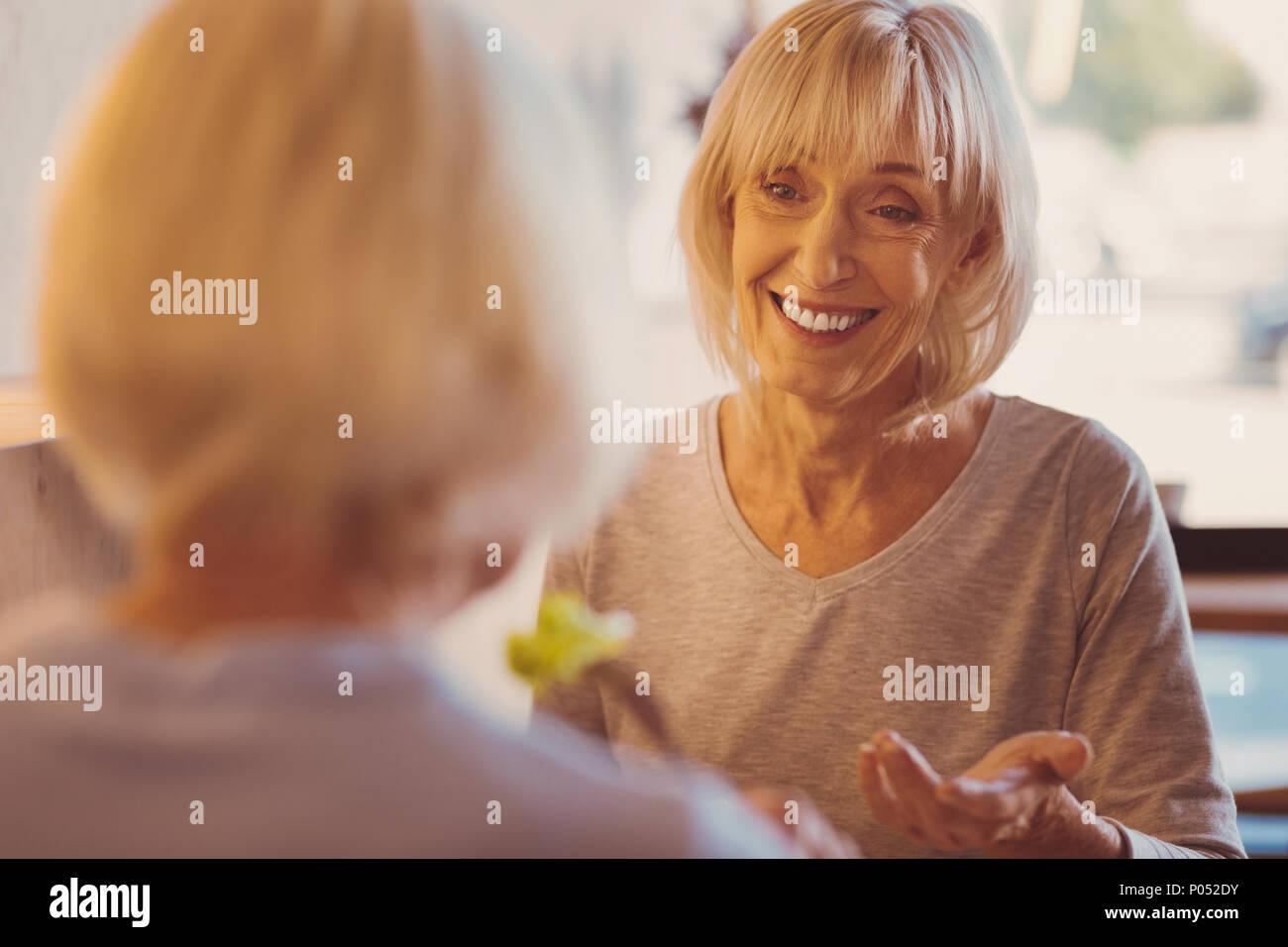 Fröhliche Frau erzählt ihrer Freundin news beim Brunch im Cafe Stockbild