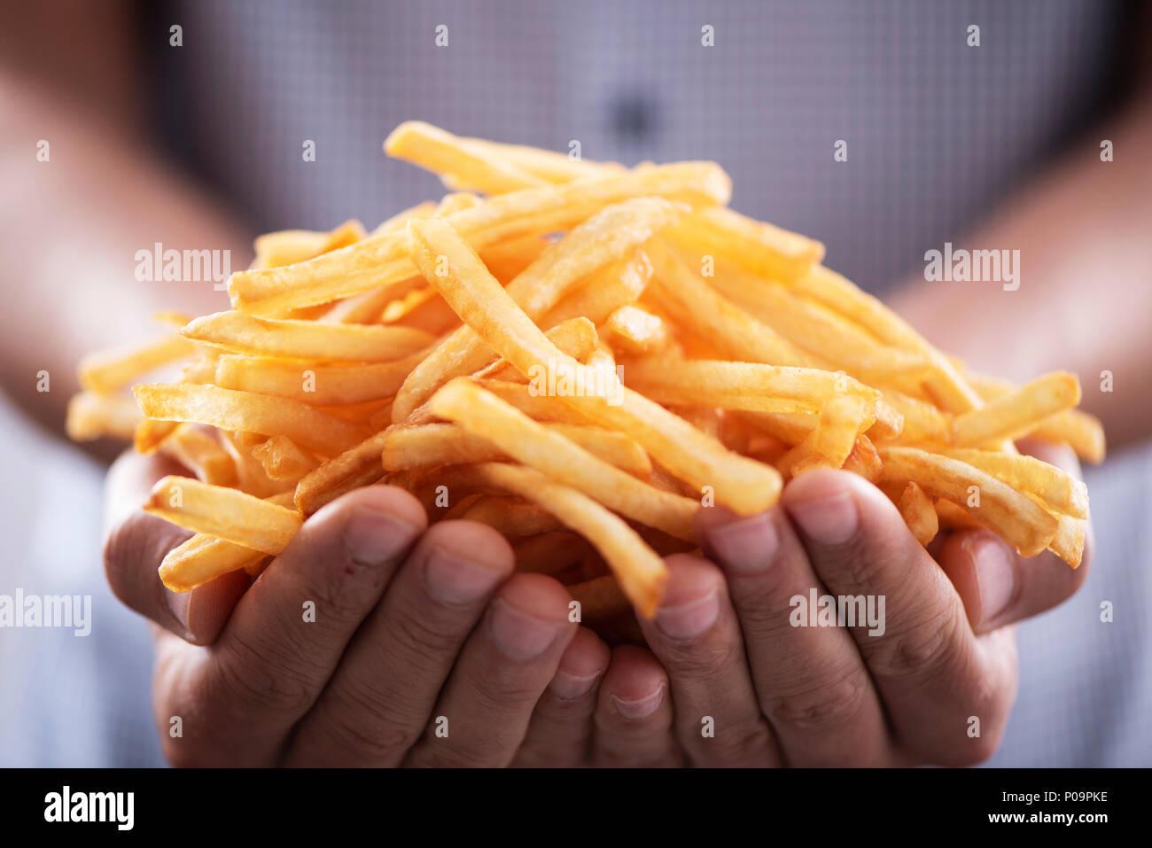 Nahaufnahme eines jungen kaukasischen Mann mit ein paar leckere Pommes frites in seine Hände Stockbild
