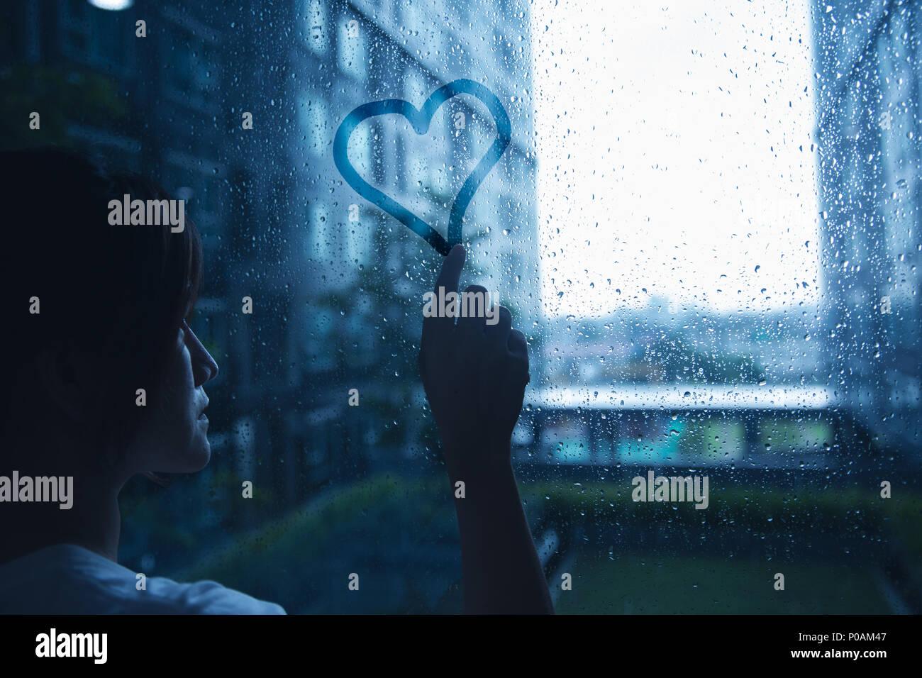 Traurig einsam liebe Frau in Regen Herz auf Fenster Glas dunkelblau Ton Stockbild