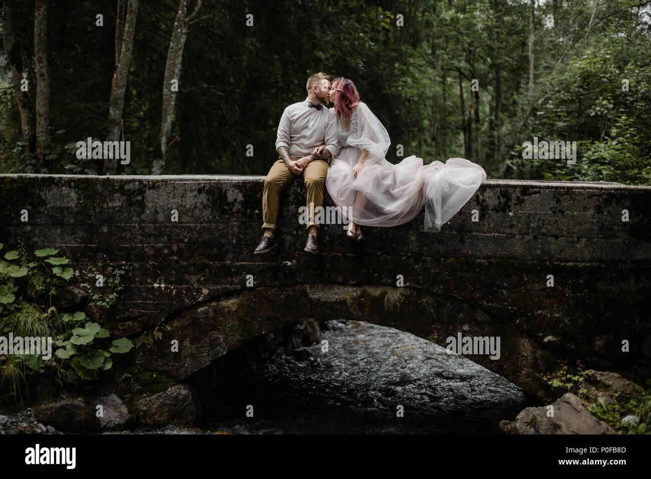 Schöne junge Hochzeit paar Küssen, beim Sitzen auf der Brücke über den Fluss die Berge in den Alpen Stockbild