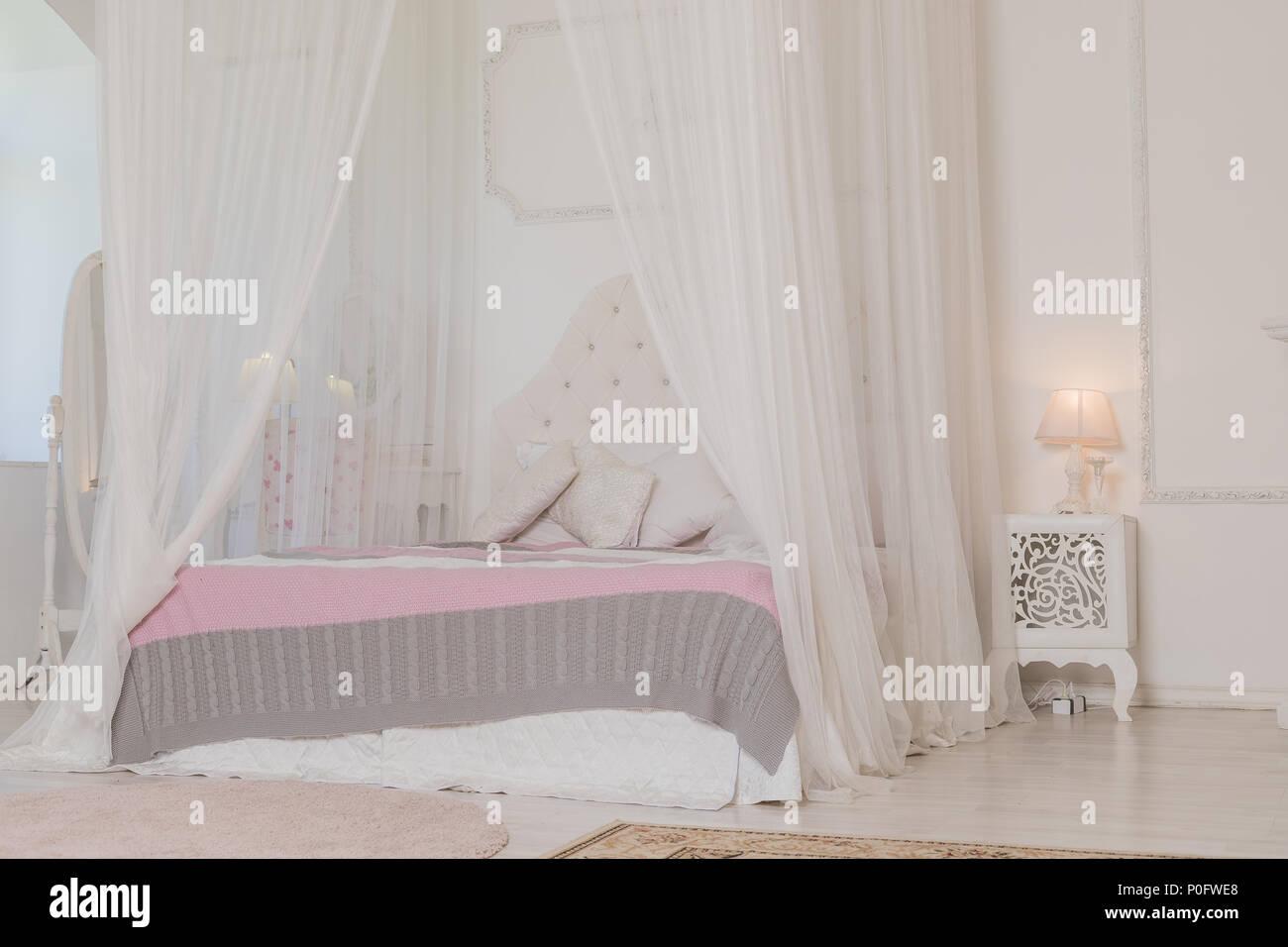 Schlafzimmer In Sanften Hellen Farben Mit Holzfußboden. Großes Bequemes  Himmelbett Doppelbett In Eleganten Klassischen Schlafzimmer.