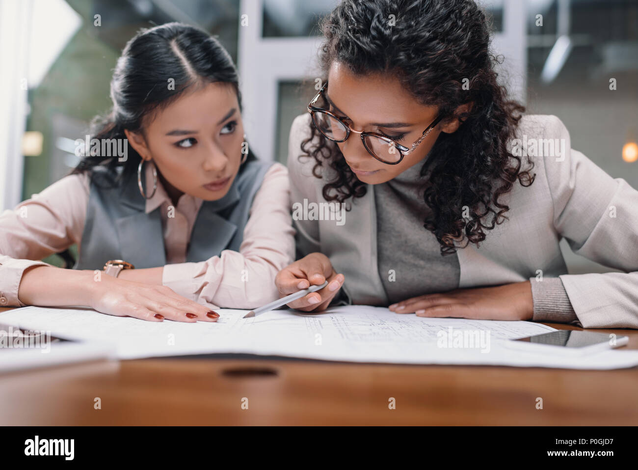 Konzentriert multiethnischen Unternehmerinnen Arbeiten mit Dokumenten in Office Stockbild