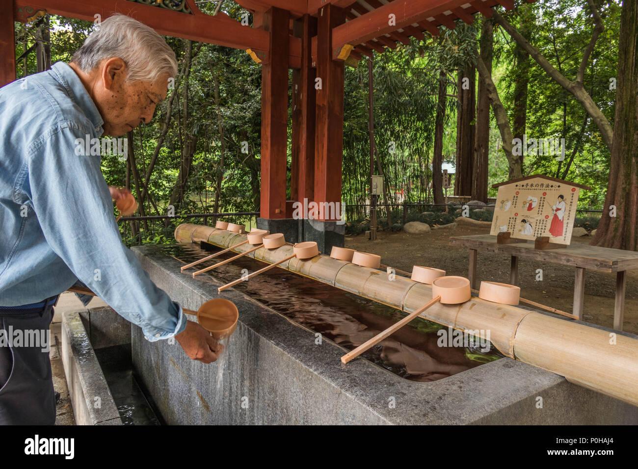 Vor der Eingabe eines Shinto Schrein Besucher selbst mit Wasser an der temizuya reinigen. Ein Mann wäscht seine Hände mit Bambus Pendelarm, Hikawa Jinja Schrein Stockfoto