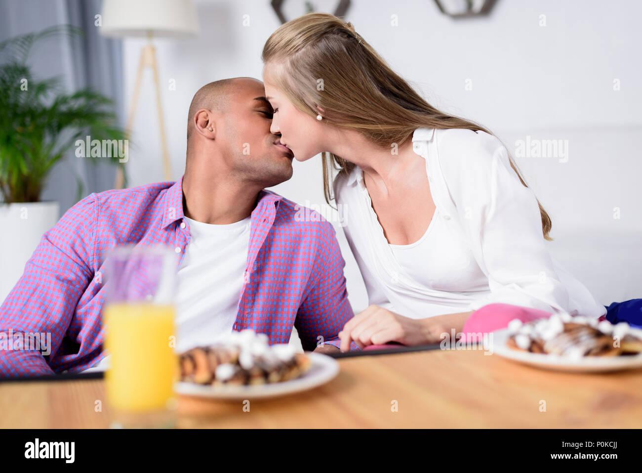 Multikulturelle Paare küssen in der Nähe der Tisch mit dem Essen Stockbild