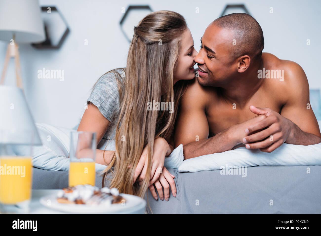 Multikulturelle Paare küssen und liegend auf Bett Stockbild