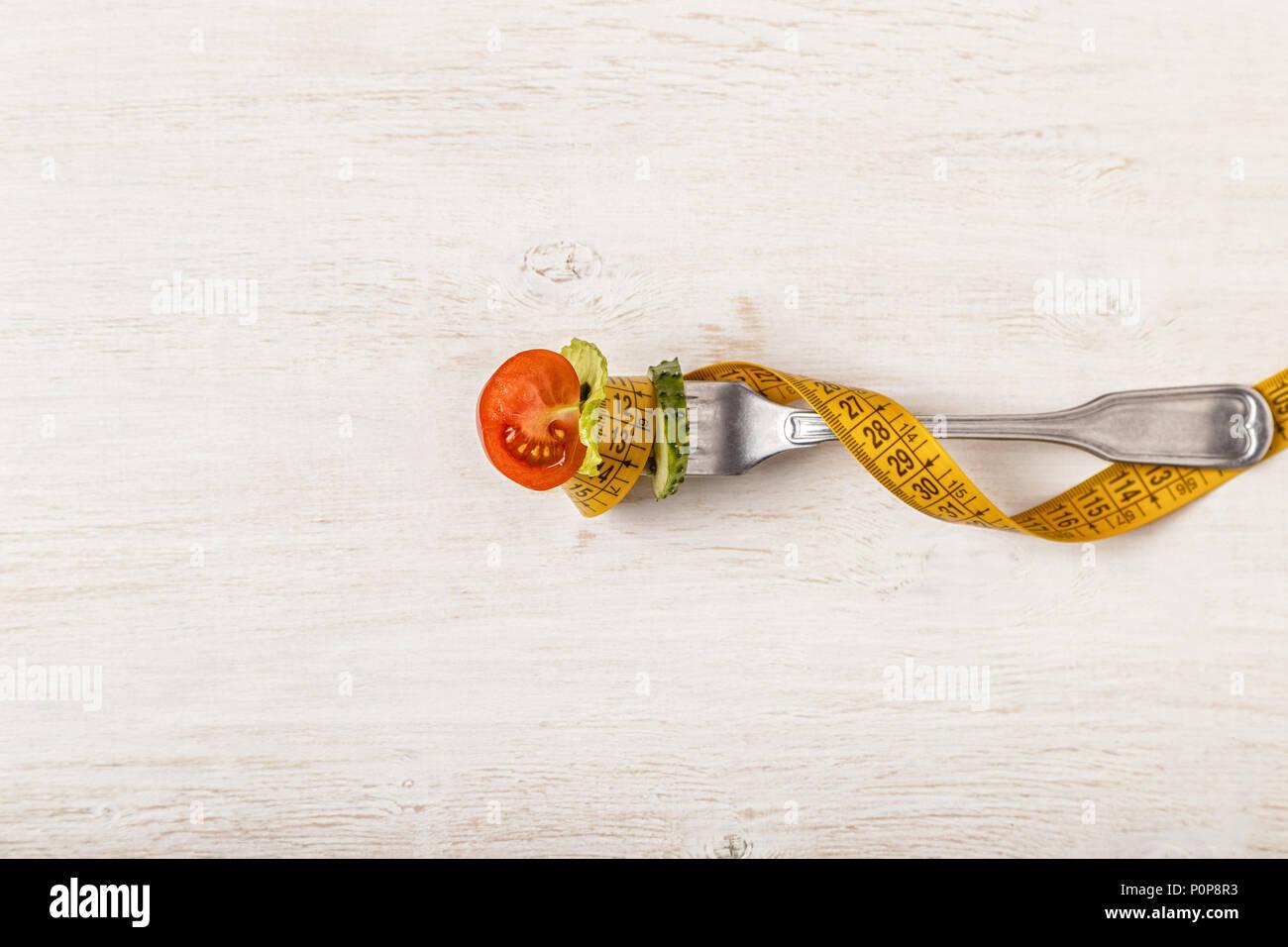 Frischer Salat auf einer Gabel, Maßband, Ansicht von oben. Das Konzept der Ernährung, gesundes Essen Stockbild