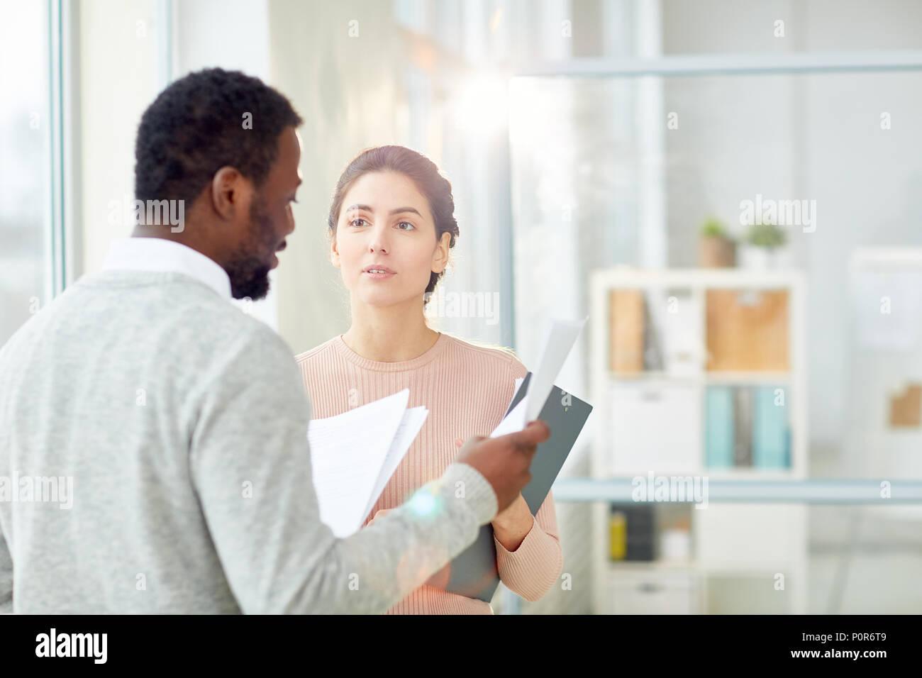 Bärtige Afrikanische amerikanische Unternehmer Studium der Statistik Daten mit Jungen untergeordnete beim Stehen bei modernen Großraumbüro, lens flare Stockbild