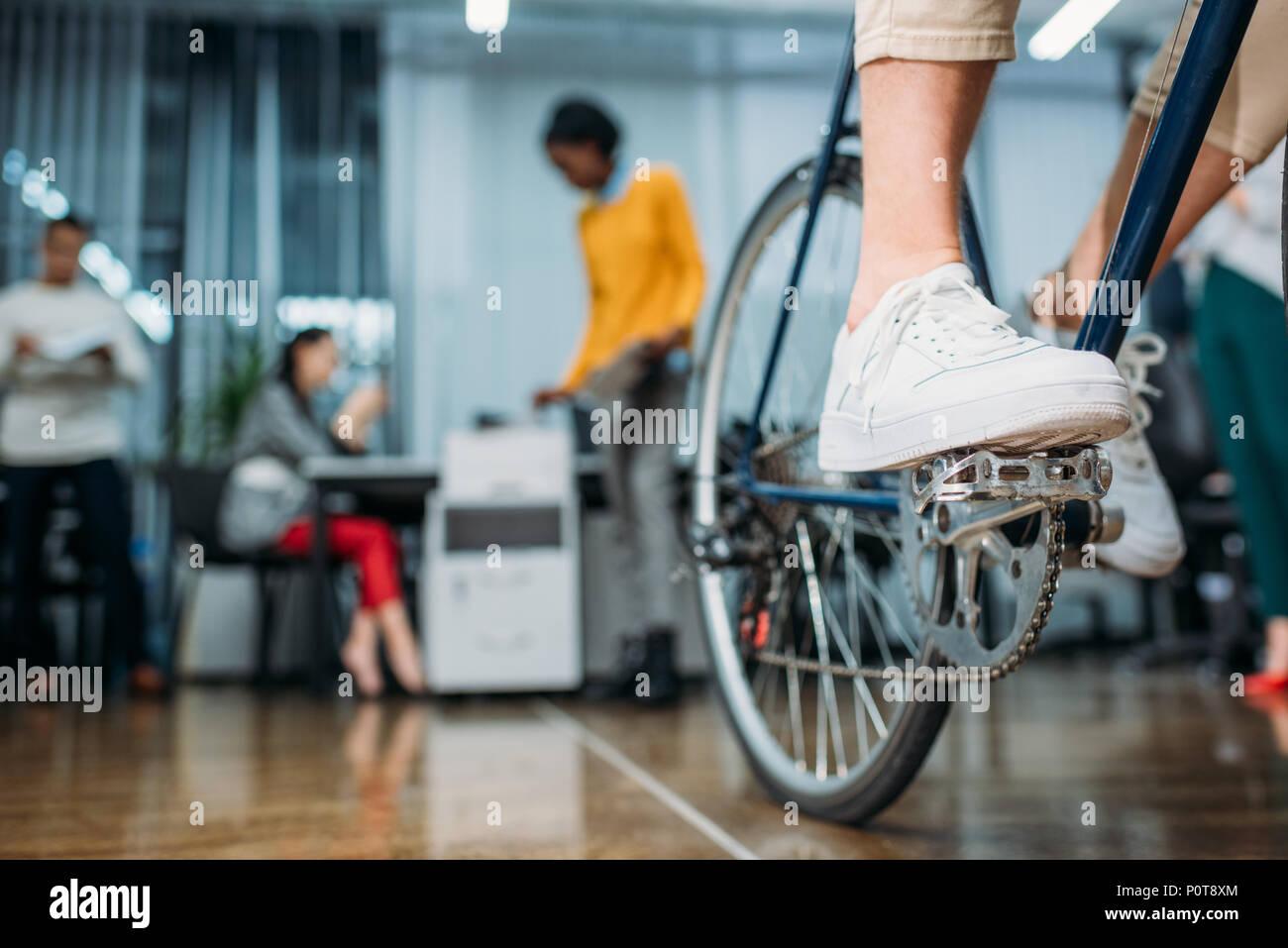 7/8 Schuß von person Reiten Fahrrad an moderne Büro Stockfoto