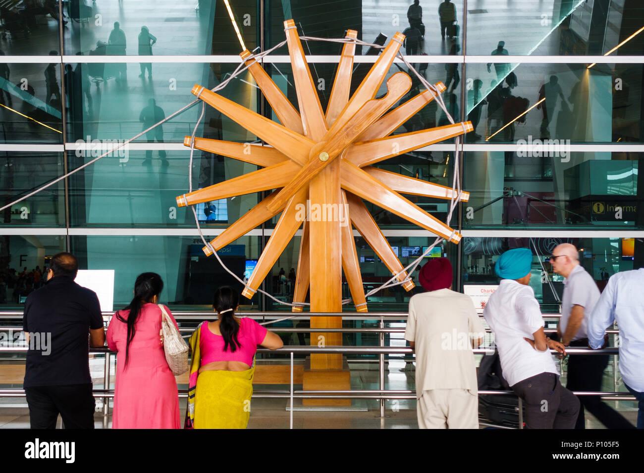 NEW DELHI, INDIEN - ca. April 2017: Menschen stehen vor der weltweit größten charkha (Spinnrad) an Indira Gandhi International Airport. Stockfoto