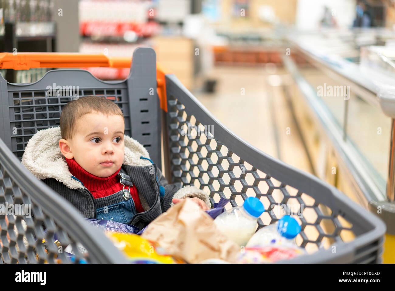 8ffe3907e96325 Volle Einkaufswagen mit Lebensmitteln im Supermarkt. In der Karre sitzt ein  Baby.