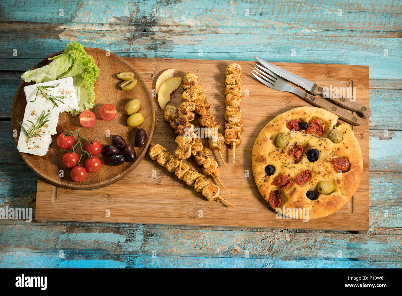 Gegrillete Fleischspiesse, mediterranes Ofenbrot mit Oliven und getrockneten Tomaten, Schafskäse mit Rosmarin und Salatblättern garniert, Studio Stockbild