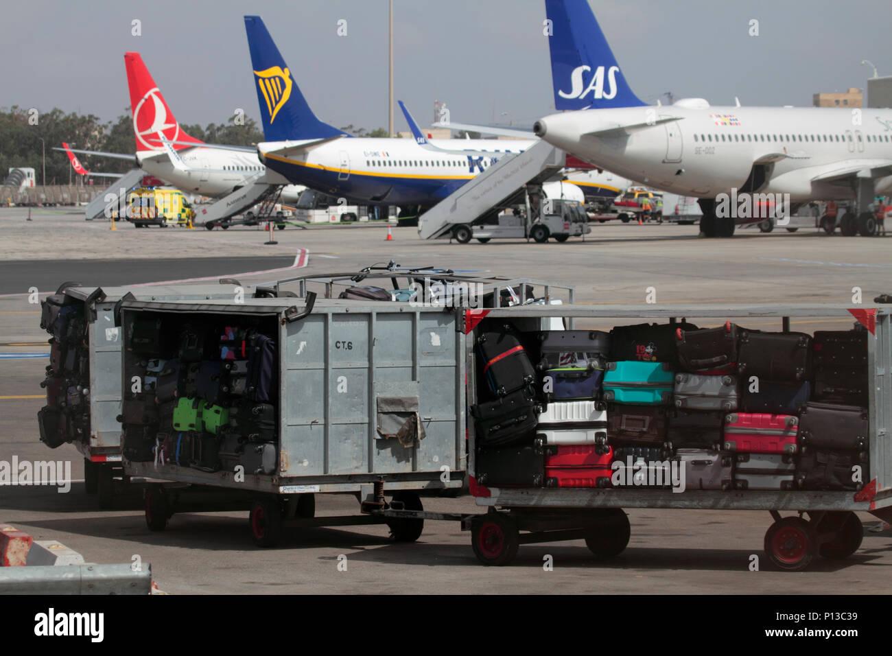 Gepäckwagen warten auf ein Flugzeug auf dem Vorfeld am internationalen Flughafen Malta geschleppt werden. Der Umgang mit dem Gepäck und Flugverkehr am Flughafen. Stockbild