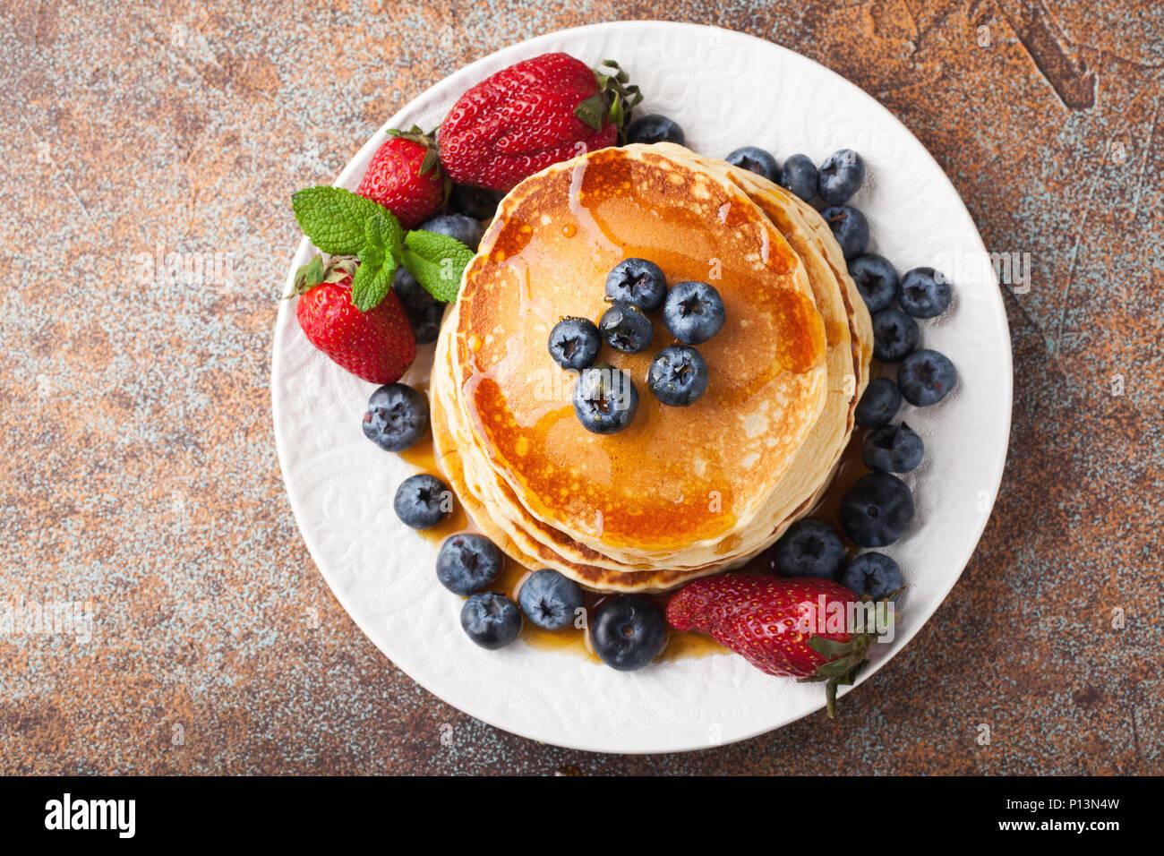Close-up leckere Pfannkuchen mit frischen Heidelbeeren, Erdbeeren und Ahornsirup auf einem rostigen Hintergrund. Mit kopieren. Ansicht von oben. Stockbild