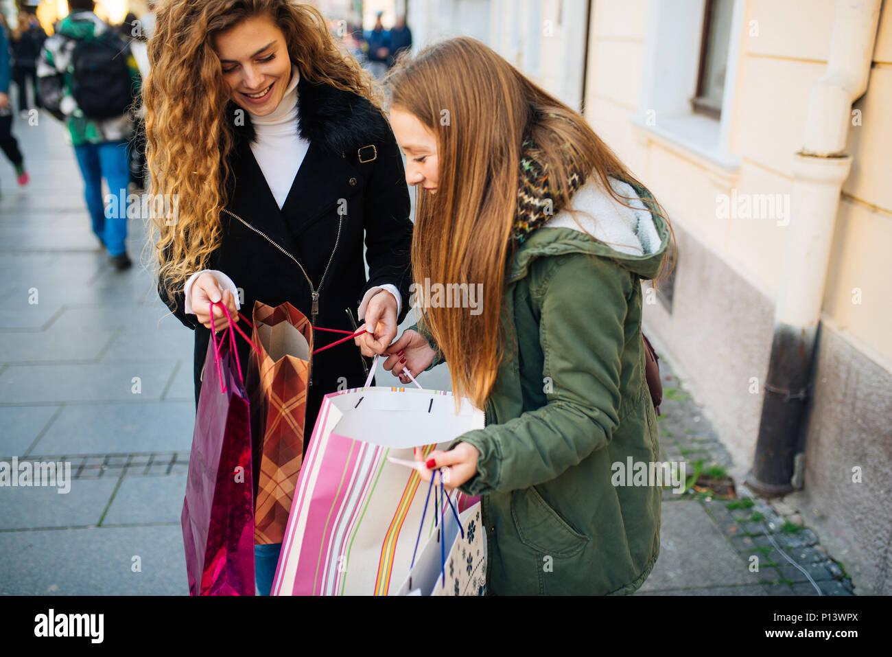 Junge attraktive Frau mit Santa Claus hat vor Schaufenster auf der Suche etwas zu kaufen Stockbild