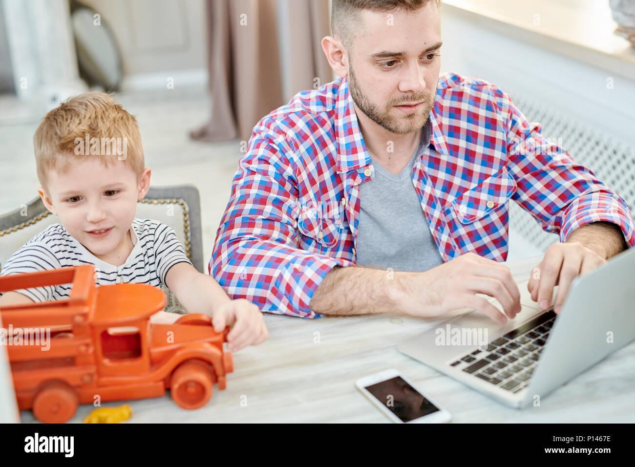 Junger Vater von zu Hause aus arbeiten Stockbild