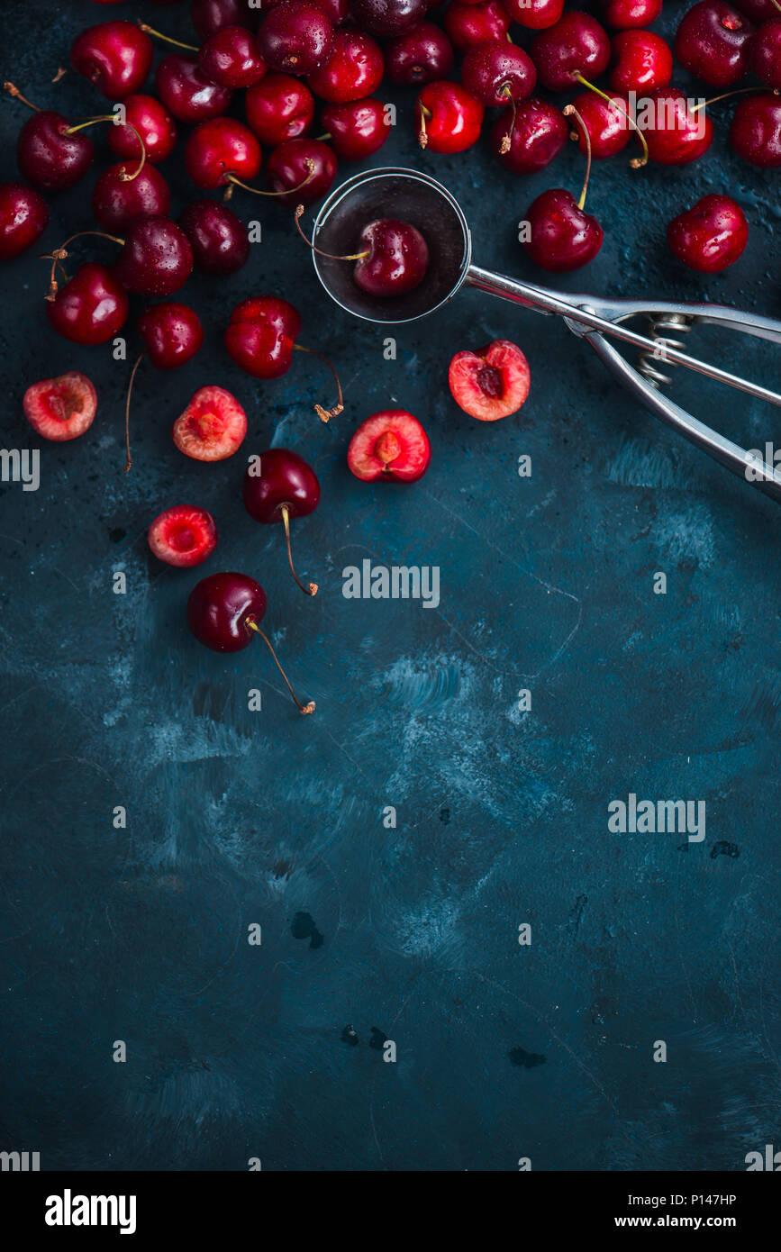 Kirschen und Eis Löffel auf grauem Beton Hintergrund, Sommer Beeren Konzept mit kopieren. Die dessert Flach in neutralen Farbtönen Stockbild
