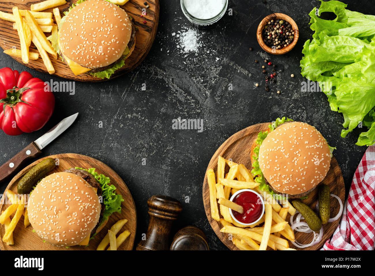 Burger, Hamburger, Pommes Frites und frischem Gemüse. BBQ party food. Dunkler Hintergrund, Ansicht von oben kopieren und Platz für Text. Sommer Grill Konzept Stockbild