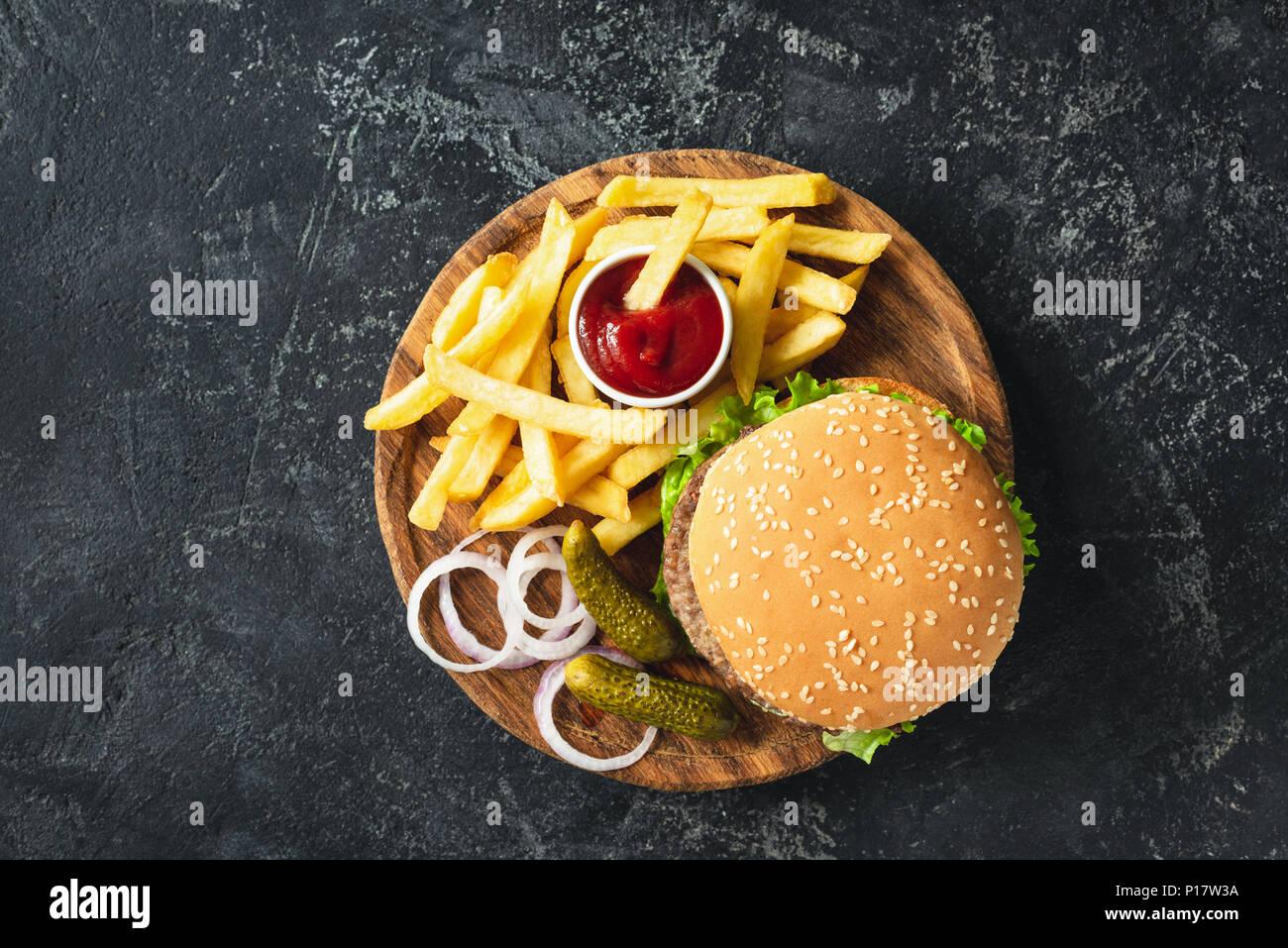 Burger, Hamburger oder Cheeseburger mit Pommes Frites, Essiggurken und Zwiebeln auf Holzbrett serviert. Ansicht von oben. Fast food Konzept Stockbild