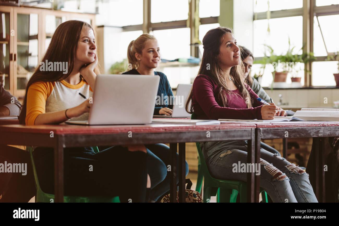 Aufmerksam hören die Schüler in einem Klassenzimmer, einen Vortrag zu halten. Junge Menschen studieren an der Universität. Stockbild