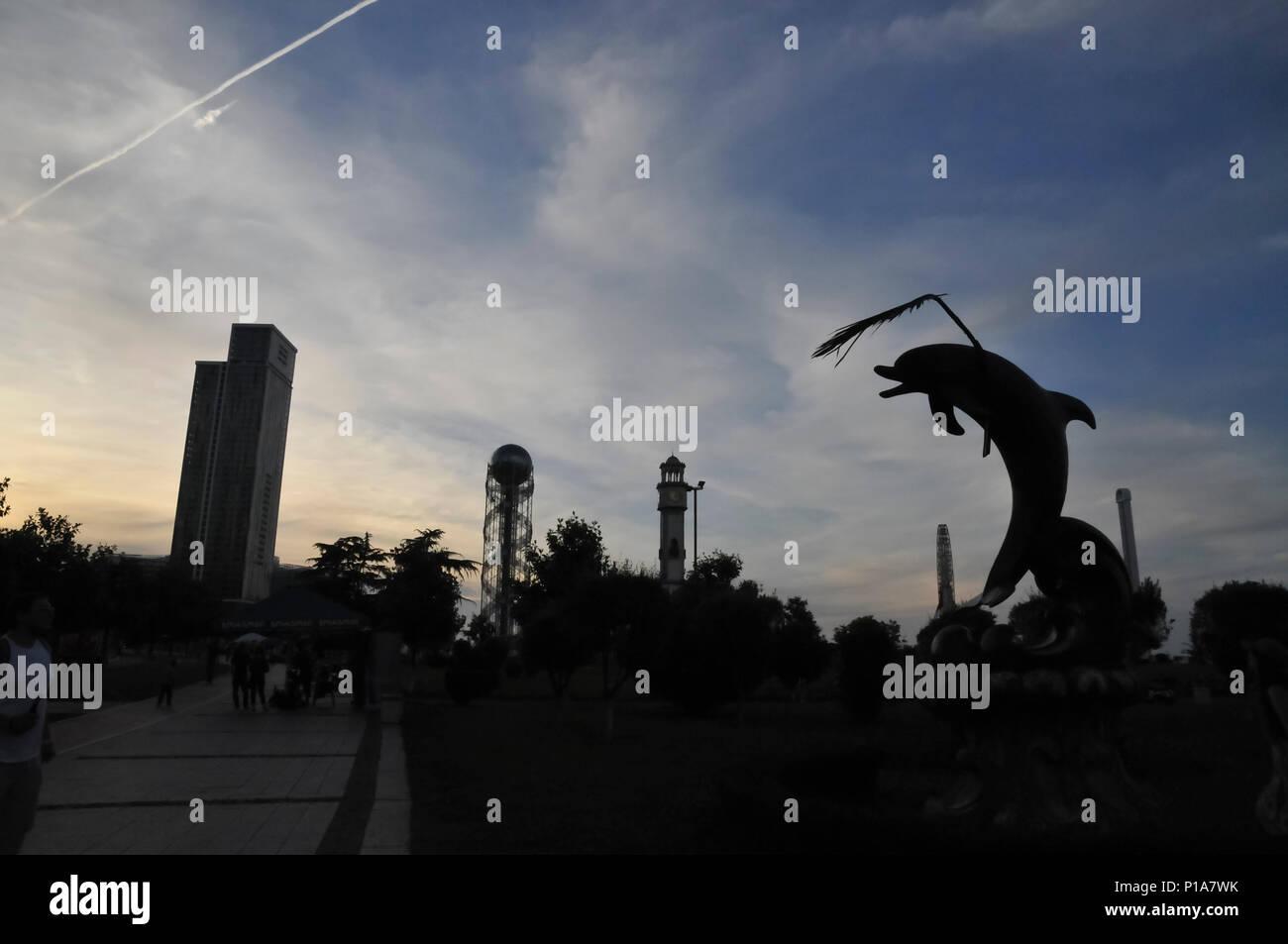 Silhouette der Delphin Statue in Wunder Park in der Abenddämmerung. Alphabetische Tower und der Old Clock Tower im Hintergrund. Batumi, Georgien Stockfoto