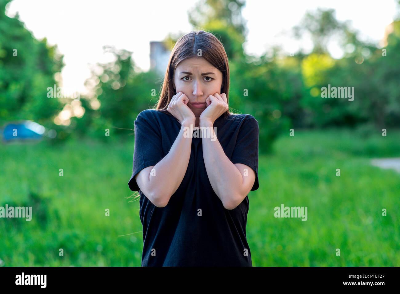 Schöne brünette Mädchen. Im Sommer im Park auf Urlaub. Emotionale Mimik, fürchte ich. Angst Frau. Stockbild