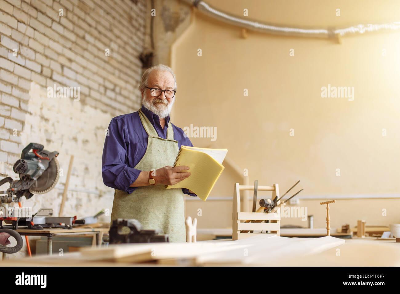 Art Opa schaut in die Kamera in der Werkstatt Stockbild