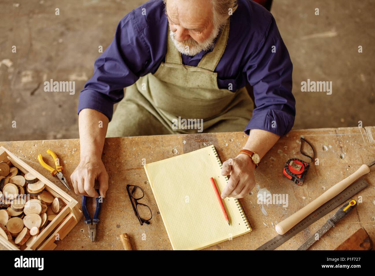 Senioren am Schreibtisch, die mit Instrumenten durcheinandergeworfen Sitzt Stockbild