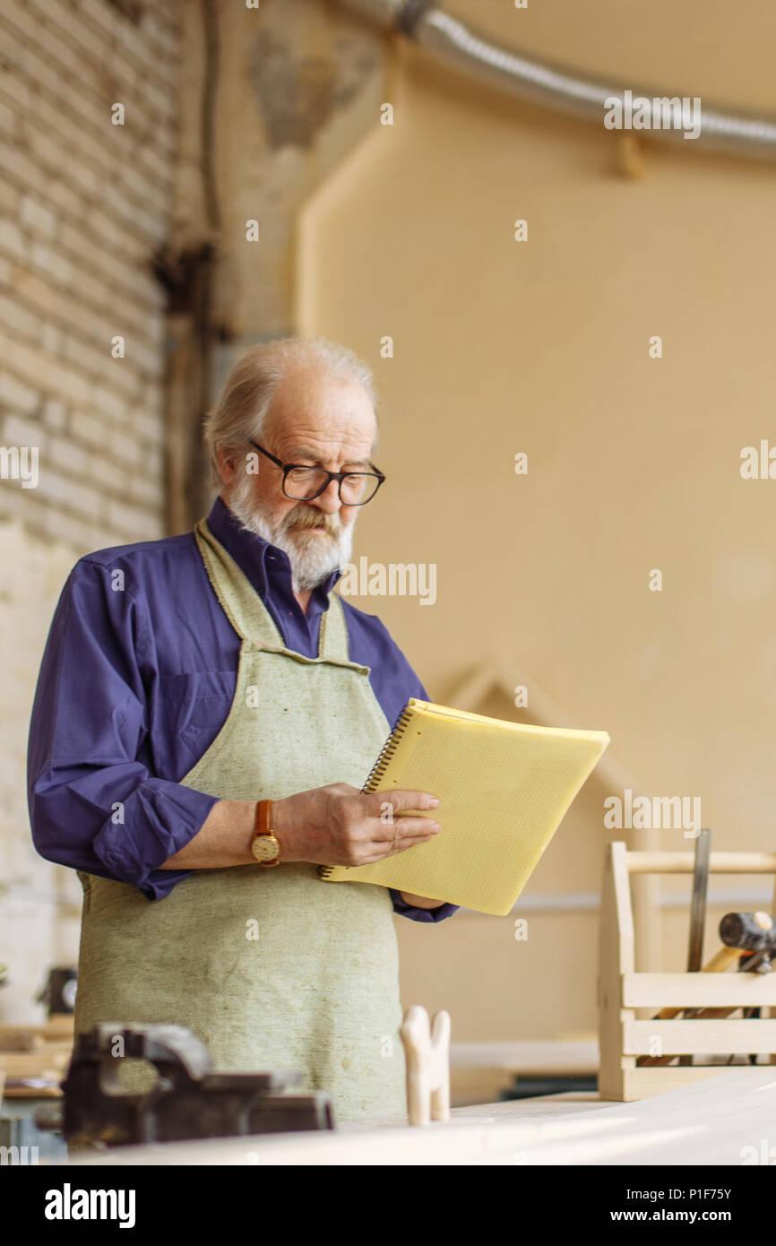 Close-up Seitenansicht schoss der älteren Mann mit Übung Buch in seinem Arbeitszimmer Stockbild
