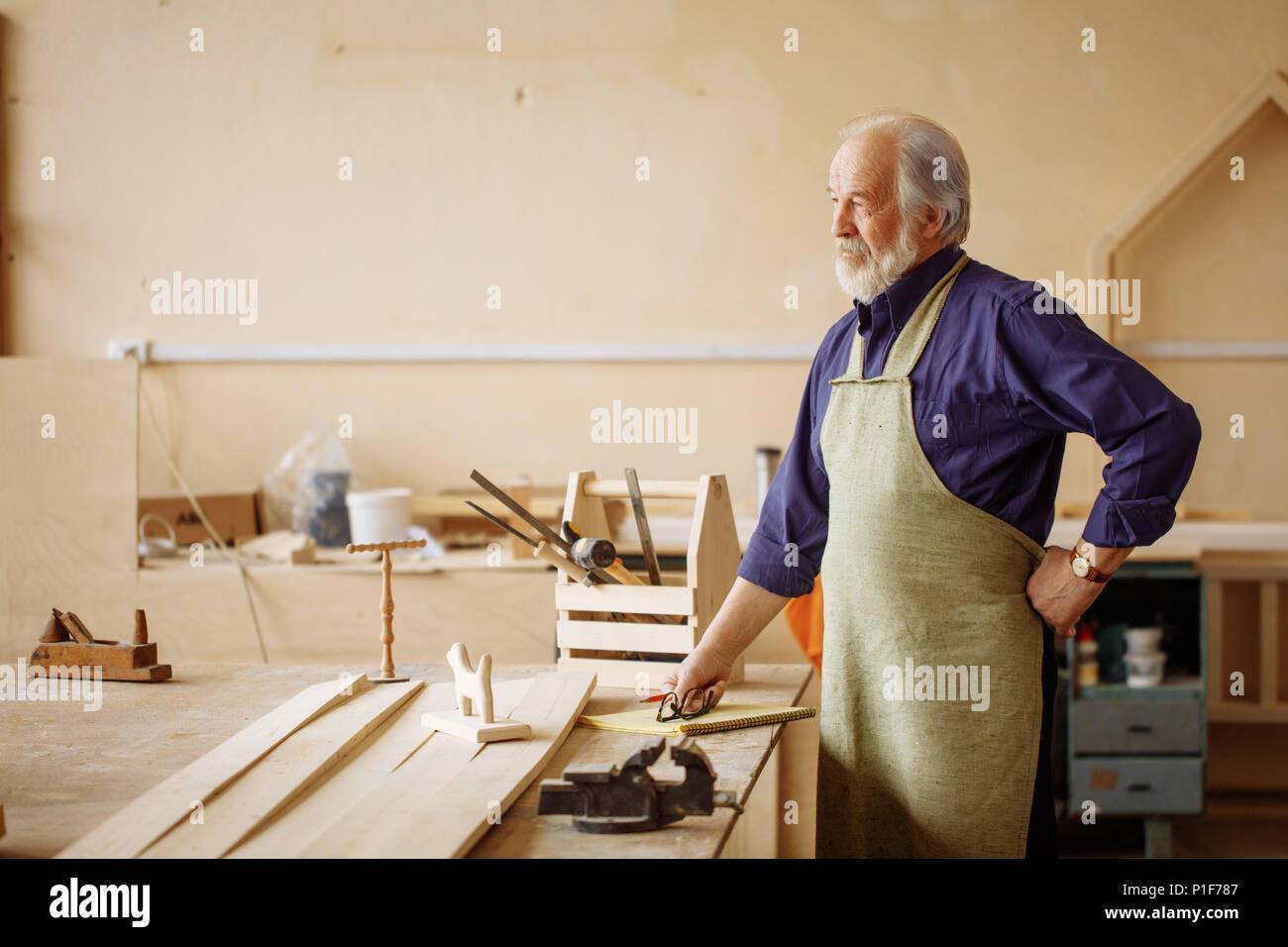 Nahaufnahme Seitenansicht Bild von müde, nachdenklich, Rentner in der Reparaturwerkstatt Stockbild